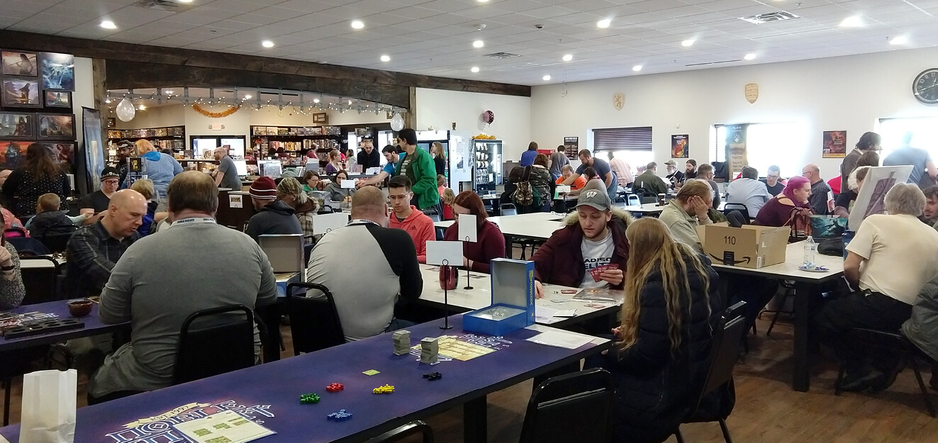 A large room of people play games at tables