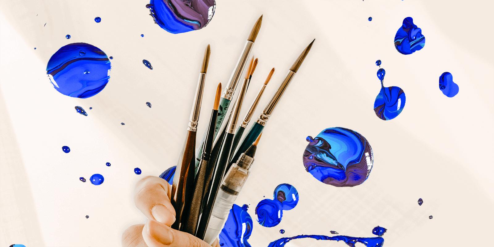 Hand holding paint brushes