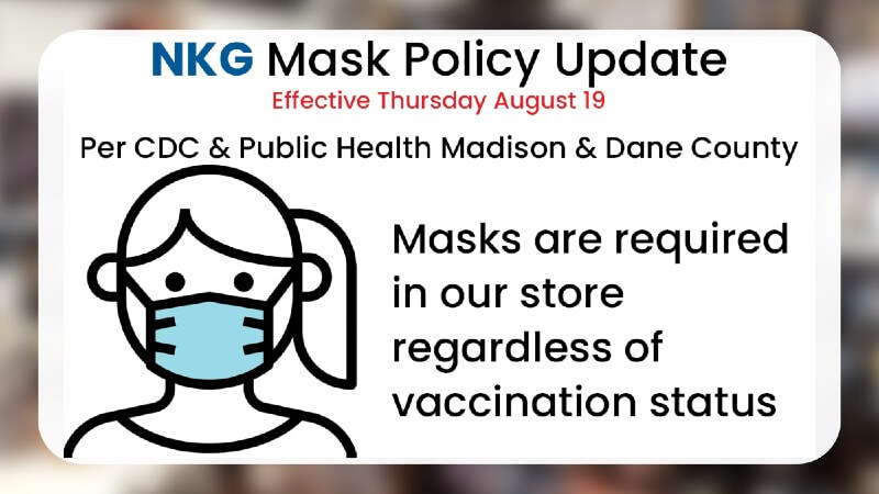 Noble Knight Games mask policy update sign showing a cartoon masked face noting that masks are required in the store regardless of vaccination status