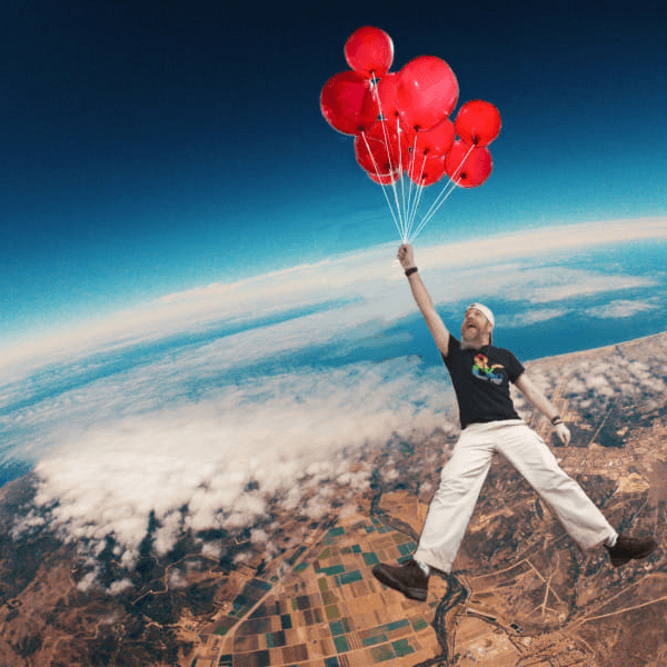 SteviL of Noble Knight Games is shown as a tall man in a Dungeons & Dragons logo tee, holding a bunch of red balloons by the string, while he floats happily miles above the earth
